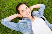 Smiling young girl lying on grass — Stock Photo