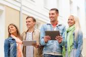 Group of smiling friends with tablet pc computers — Stock Photo