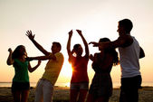 Smiling friends dancing on summer beach — Stock Photo