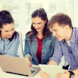 Three smiling students with laptop and tablet pc — Stock Photo #52918863