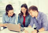 Three smiling students with laptop and tablet pc — Foto Stock