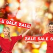 Smiling man and woman with red sale signs — Stock Photo #52921699