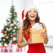Smiling woman in santa helper hat with gift box — Stock Photo #52923403