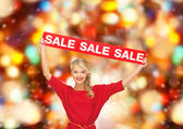 Woman in red dress with sale sign — Stock Photo