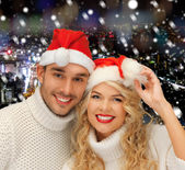 Smiiling couple in sweaters and santa helper hats — Foto Stock