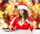 Smiling woman with credit card and tablet pc — Stock Photo
