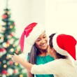 Hugging mother and daughter in santa helper hats — Stock Photo #52962827
