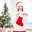 Woman in santa hat with gift box and stocking — Stock Photo #52963235