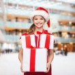 Smiling little girl in santa helper hat with gifts — Stock Photo #53076477