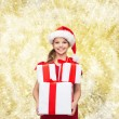Smiling little girl in santa helper hat with gifts — Stock Photo #53076515