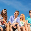 Group of smiling friends sitting on city street — Stock Photo #53079197
