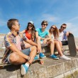 Group of smiling friends sitting on city street — Stock Photo #53079789