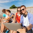 Group of smiling friends with tablet pc outdoors — Stock Photo #53079913