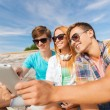 Group of smiling friends with tablet pc outdoors — Stock Photo #53079929