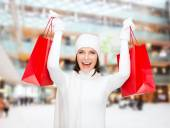 Smiling young woman with red shopping bags — Stock Photo