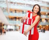 Gülümseyen hediye kutuları ile kırmızı elbiseli kadın — Stok fotoğraf