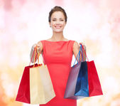 Smiling elegant woman in dress with shopping bags — Stockfoto