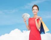 Lächelnde frau im roten kleid mit einkaufstüten — Stockfoto