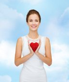 Smiling woman in white dress with red heart — Stockfoto
