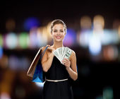 Smiling woman in dress with shopping bags — Stockfoto