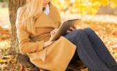 Young woman with tablet pc in autumn park — Stock Photo