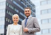 Smiling businessmen standing over office building — Stock Photo