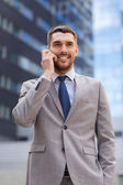 Smiling businessman with smartphone outdoors — Stock Photo
