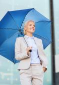 Young smiling businesswoman with umbrella outdoors — Stockfoto