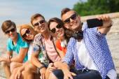 Group of smiling friends with smartphone outdoors — Stock Photo
