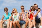 Group of smiling friends with smartphones outdoors — Stock Photo