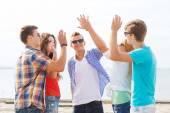 Group of smiling friends making high five outdoors — Photo