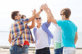 Group of smiling friends making high five outdoors — Stock Photo