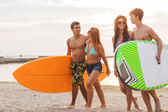 Smiling friends in sunglasses with surfs on beach — Stock Photo