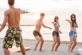 Usmívající se přátelé v sluneční brýle s surfuje na pláži — Stock fotografie