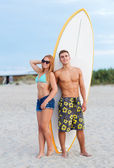 Smiling couple in sunglasses with surfs on beach — 图库照片