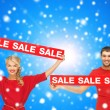 Smiling man and woman with red sale signs — Stock Photo #53129087