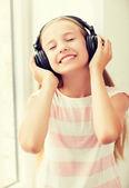 Kleines mädchen mit kopfhörern zu hause — Stockfoto