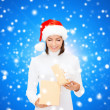 Smiling woman in santa helper hat with gift box — Stock Photo #53130955