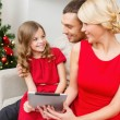 Smiling family with tablet pc — Stock Photo #53136329