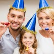 Smiling family in blue hats blowing favor horns — Stock Photo #53137159