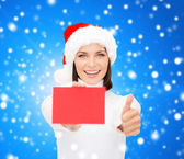Woman in santa helper hat with blank red card — Stock Photo