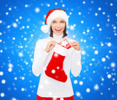 Woman in santa hat with gift box and stocking — Stock Photo