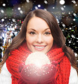 Smiling woman in winter clothes with snowball — Stock Photo