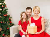 Smiling family holding gift box — Stock Photo