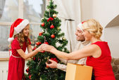 Smiling family decorating christmas tree — Stock Photo
