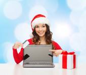Smiling woman with credit card and laptop — Stockfoto