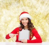 Smiling woman in santa hat with gift and tablet pc — Stockfoto