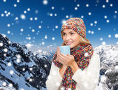 Smiling young woman in winter clothes with cup — Stockfoto