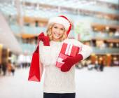 Smiling young woman in santa helper hat with gifts — Stock Photo