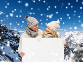 Smiling couple in winter clothes with white board — Stock Photo